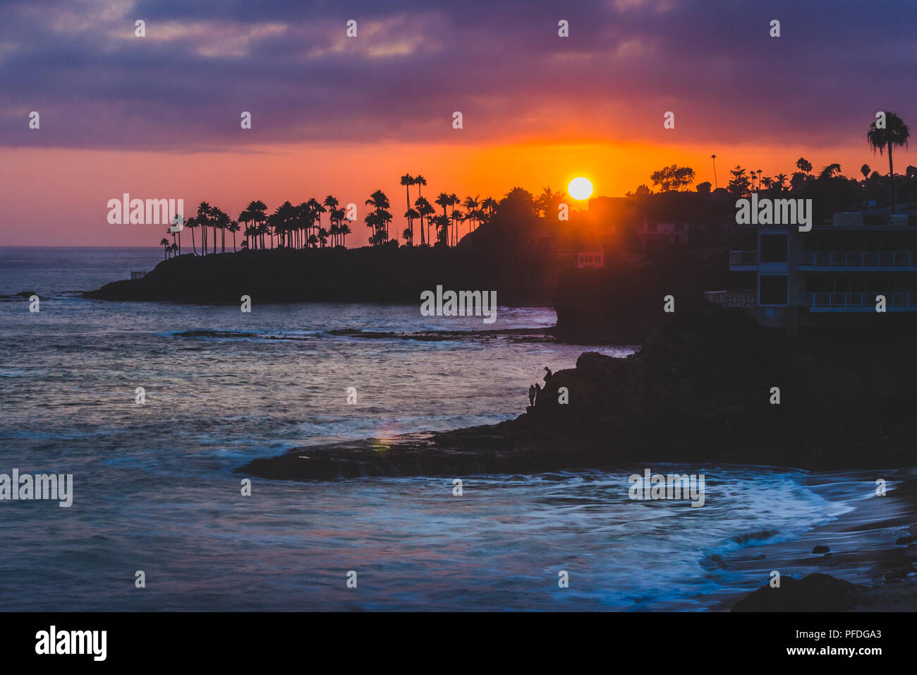 Beautiful coastal view of a colorful sky at sunset with waves crashing into rock formations and silhouette of palm trees, Divers Cove, Laguna Beach, C Stock Photo