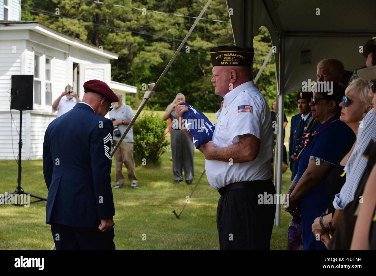 Retired New York Air National Guard 106th Rescue Wing Chief Master Sgt. Mike McManus, pararescueman NCOIC, gives the folded American Flag to the VFW 1505 Commander Mr. Mike Billinger, Keeseville, N.Y., June 13, 2018. On June 13, 1978, an HH-3E Jolly Green Giant Helicopter from the 102nd Aerospace Rescue and Recovery Group now the 106th Rescue Wing in Westhampton Beach N.Y., was returning to base after training at Plattsburgh Air Force Base, N.Y. After encountering inclement weather, the seven members turned back to Plattsburgh, but with low visibility, the HH-3E hit the Trembleau Mountain just - Stock Image