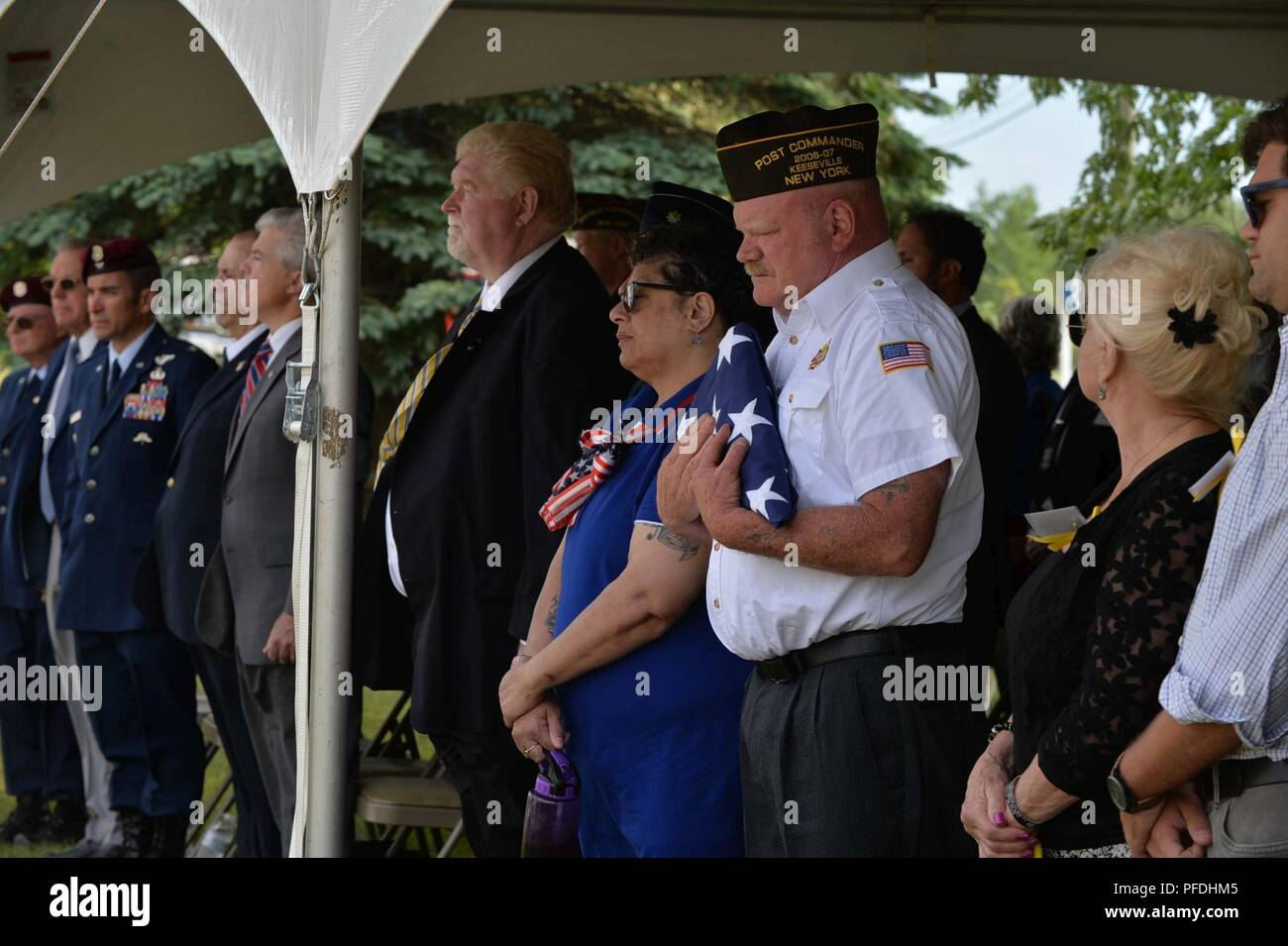 Retired New York Air National Guard 106th Rescue Wing Chief Master Sgt. Mike McManus, pararescueman NCOIC, gives the folded American flag to the VFW 1505 Commander, Mr. Mike Billinger, Keeseville, N.Y., June 13, 2018. On June 13, 1978, an HH-3E Jolly Green Giant Helicopter from the 102nd Aerospace Rescue and Recovery Group now the 106th Rescue Wing in Westhampton Beach N.Y., was returning to base after training at Plattsburgh Air Force Base, N.Y. After encountering inclement weather, the seven members turned back to Plattsburgh, but with low visibility, the HH-3E hit the Trembleau Mountain jus - Stock Image