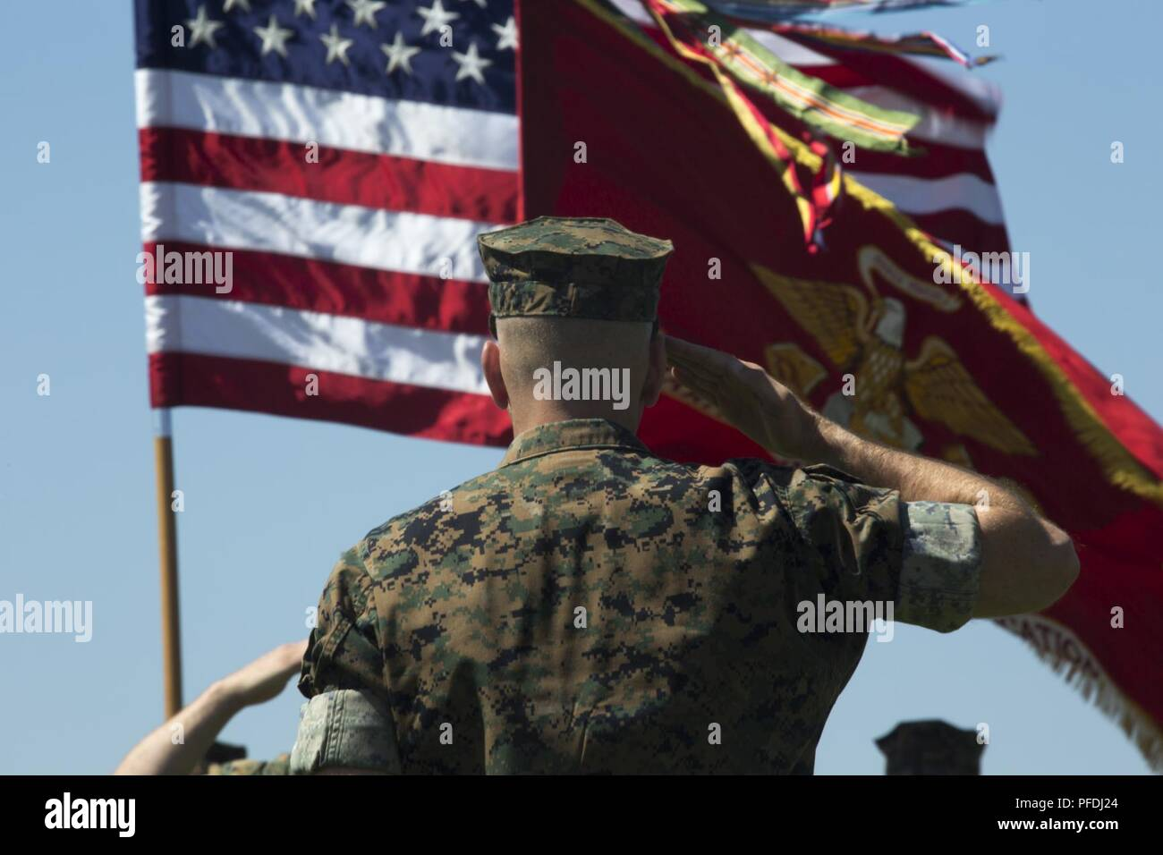 """Col. Scott A. Gondek, commanding officer of Marine Air Control Group 48, salutes the American flag as """"Star Spangled Banner"""" plays during Marine Wing Communications Squadron (MWCS) 48's change of command ceremony at Marine Corps Air Station Miramar, Calif., June 13. Lt. Col. Brian C. Pate assumed command of MWCS-48 from Lt. Col. Michael E. Sheridan who received a Meritorious Service Medal for his time as MWCS-48's commanding officer. Stock Photo"""