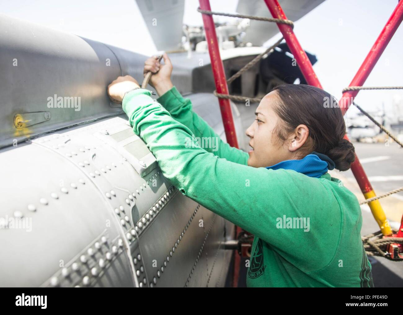 5th FLEET AREA OF OPERATIONS (June 9, 2018) Aviation Structural Mechanic 3rd Class Mileika Miki, assigned to Helicopter Sea Combat Squadron (HSC) 28, performs maintenance on an MH-60S Sea Hawk, in the hangar bay aboard the Wasp-class amphibious assault ship USS Iwo Jima (LHD 7), June 9, 2018. Iwo Jima, homeported in Mayport, Fla., is on deployment to the U.S. 5th Fleet area of operations in support of maritime security operations to reassure allies and partners, and preserve the freedom of navigation and the free flow of commerce in the region. Stock Photo