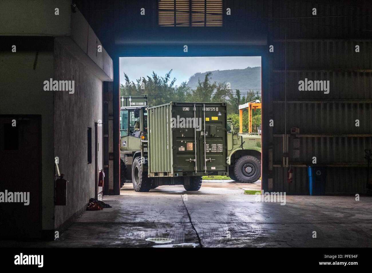 Santa Rita, Guam (June 9, 2018) Equipment Operator 2nd Class Corey Caron, assigned to Naval Mobile Construction Battalion (NMCB) 11, uses an 12k forklift to move a container with gear for the 30th Naval Construction Regiment (NCR) aboard Naval Base Guam. The 30th NCR is conducting a homeport shift from Port Hueneme, Calif. to Guam to improve command and control of subordinate units operating in the Indo-Pacific region. - Stock Image