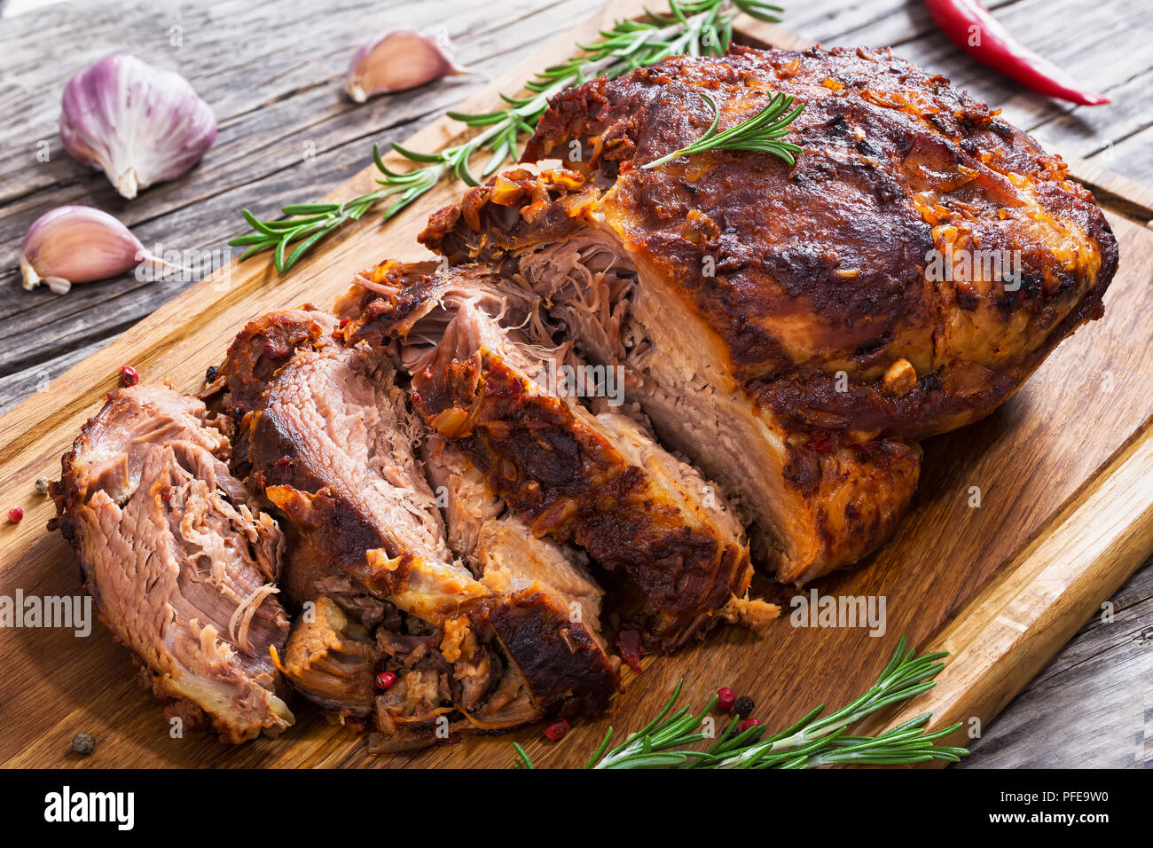 Big Piece of Slow Cooked Oven-Barbecued Pulled Pork shoulder on chopping board with mixed peppercorns, rosemary, garlic,chili on wooden planks, view f - Stock Image