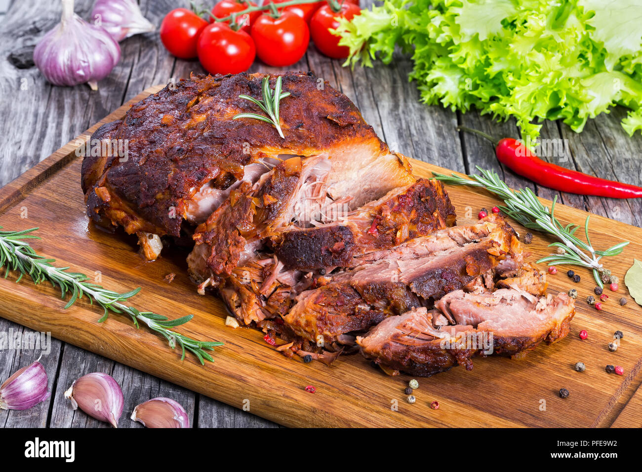 Big Piece of Slow Cooked Oven-Barbecued Pulled Pork shoulder on chopping board with mixed peppercorns, rosemary and garlic, tomato and lettuce salad o Stock Photo