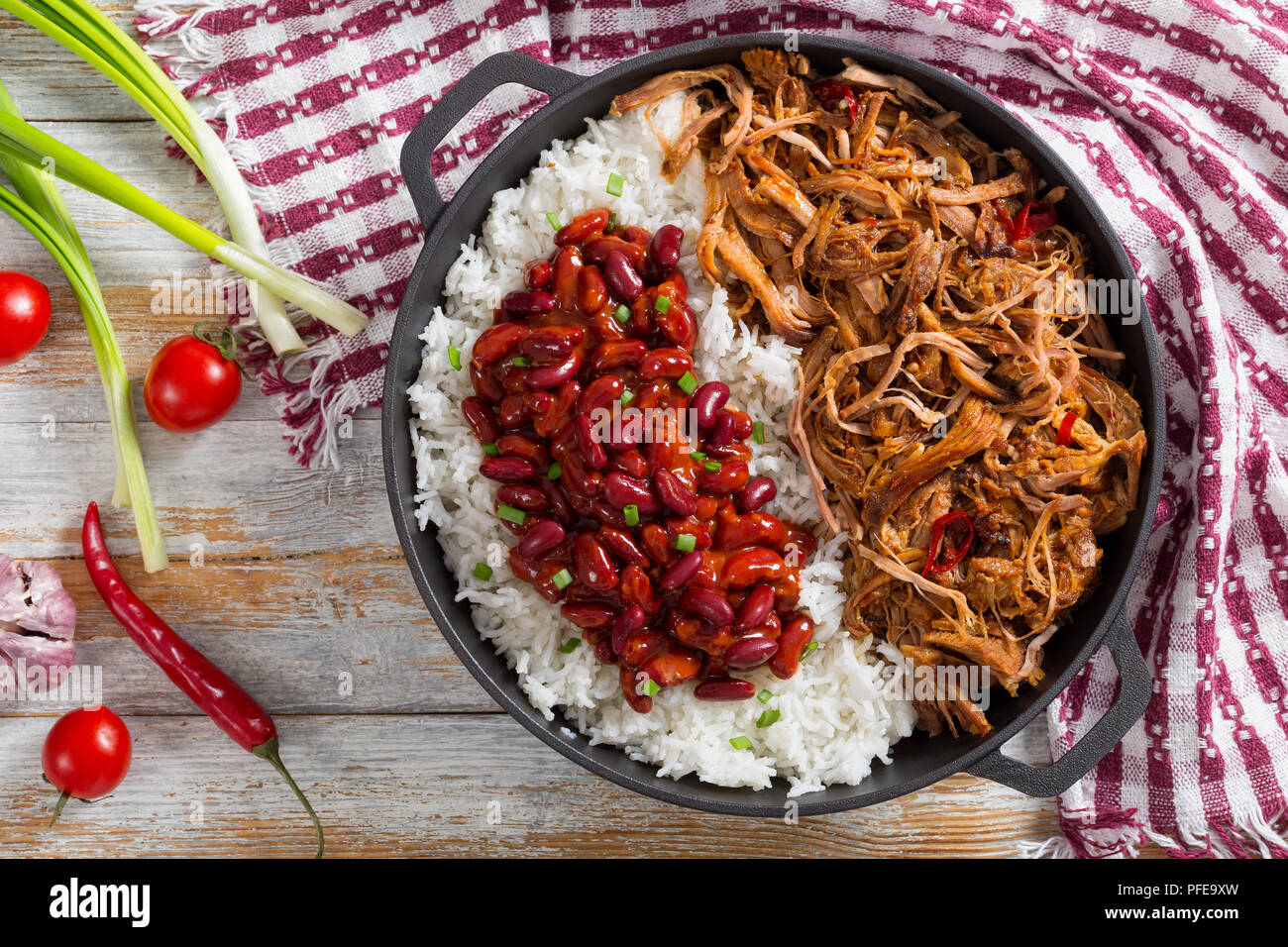 pulled slow-cooked pork shoulder with long-grain basmati rice and red bean sprinkled with green onion in stewpot with kitchen towel, on wooden table w - Stock Image
