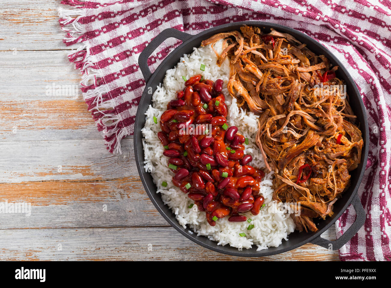 pulled slow-cooked delicious spicy meat with rice and savory Baked Beans sprinkled with green onion in stewpot with kitchen towel, on wooden table, vi - Stock Image