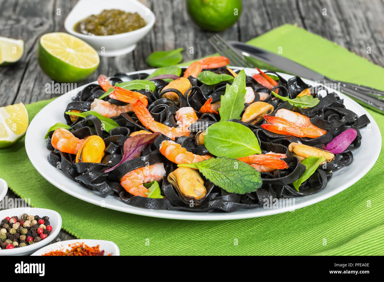 delicious black noodles salad with prawns, mussels, fresh green spinach, lettuce, arugula on white dish on table mat on dark wooden table with lime sl - Stock Image