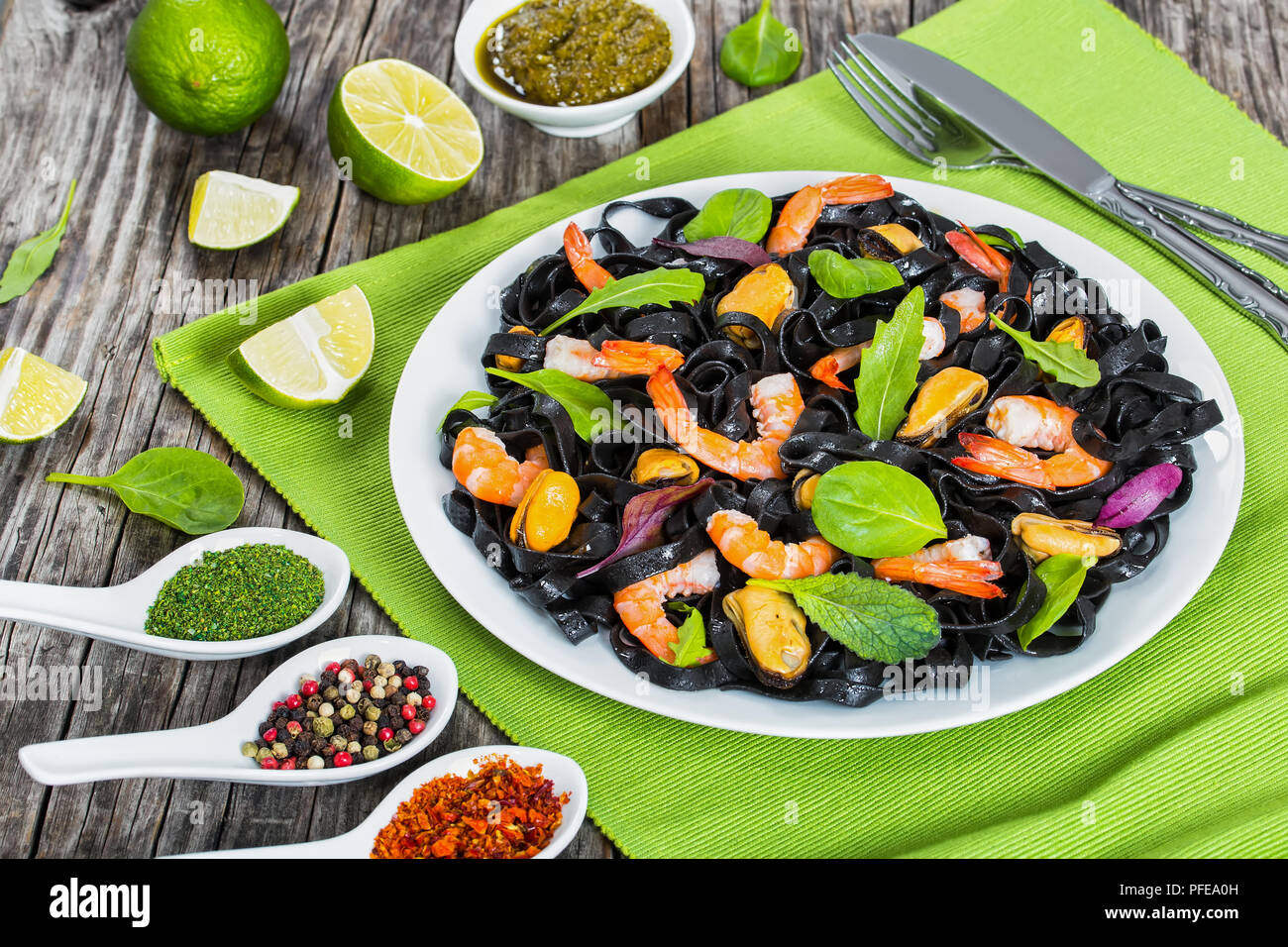 black noodles salad with prawns, mussels, fresh green spinach, lettuce, arugula on white dish on table mat on dark wooden table with lime slices and s - Stock Image