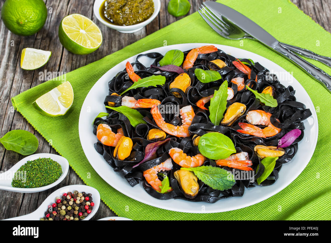 delicious black noodles salad with prawns, mussels, fresh green leaves on white dish on table mat on dark wooden table with lime and spices on backgro - Stock Image
