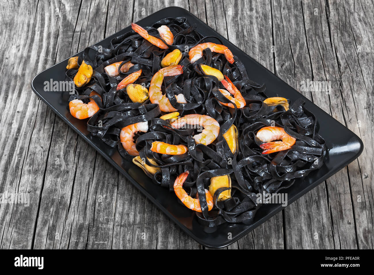 black noodles salad with prawns and mussels on black rectangular platter  on dark wooden table  close-up, top view - Stock Image
