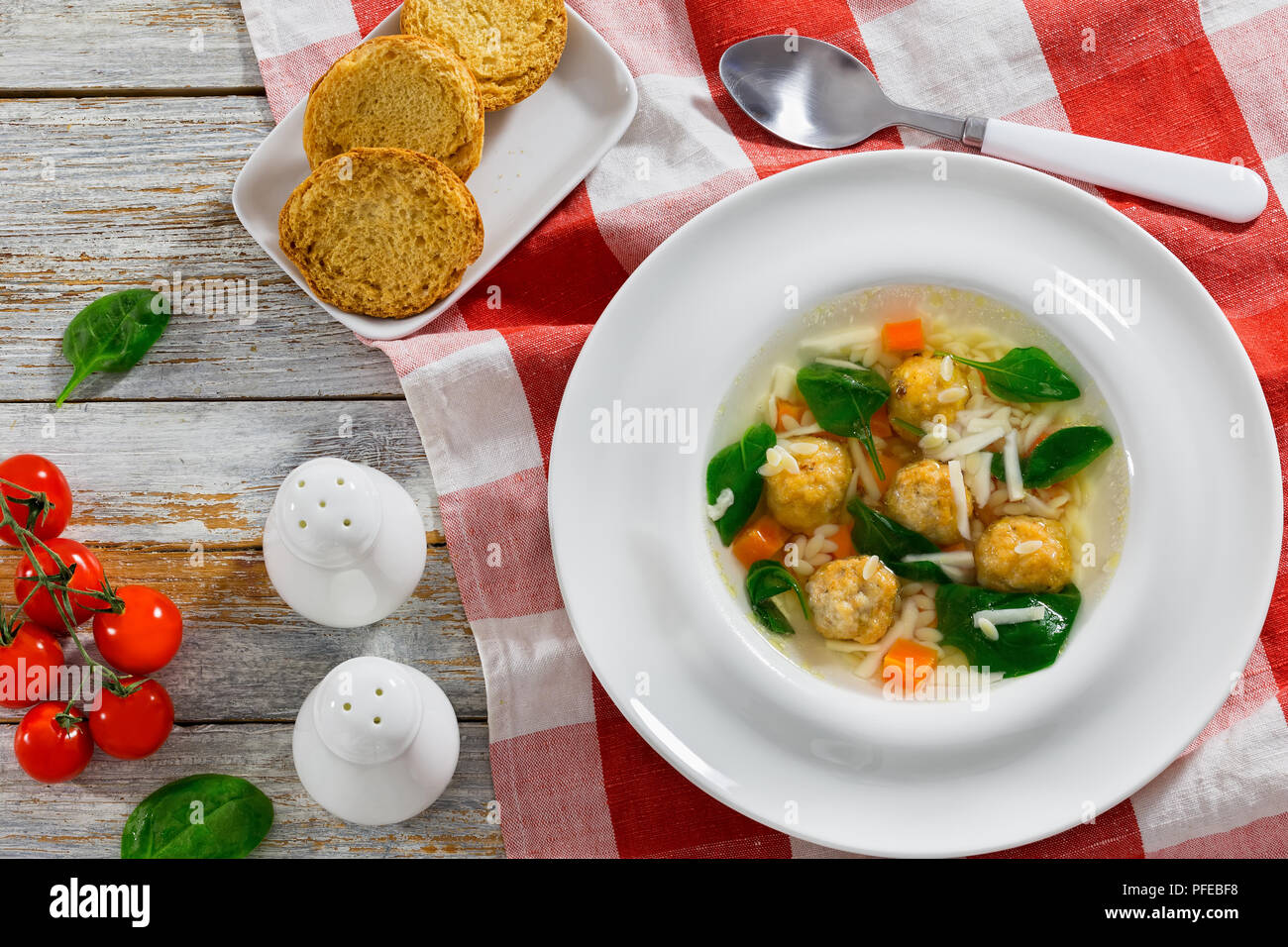 italian wedding soup with meatballs in white wide rim bowl on table cloth, salt and pepper shakers, crostini, fresh green spinach leaves and tomatoes  - Stock Image