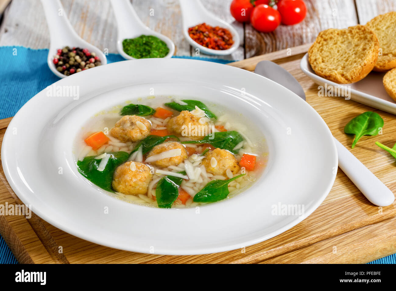 delicious wedding soup with meatball, risini pasta, carrots and spinach in white wide rim bowl with spoon on chopping board,  toasted bread crostini o Stock Photo