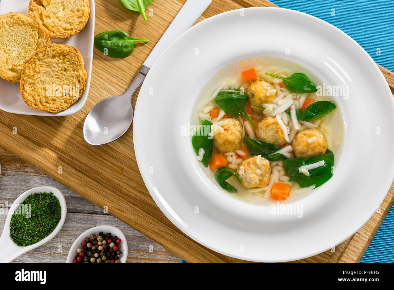 delicious wedding soup with meatball, risini pasta, carrots and spinach in white wide rim bowl with spoon on chopping board,  toasted bread crostini a - Stock Image
