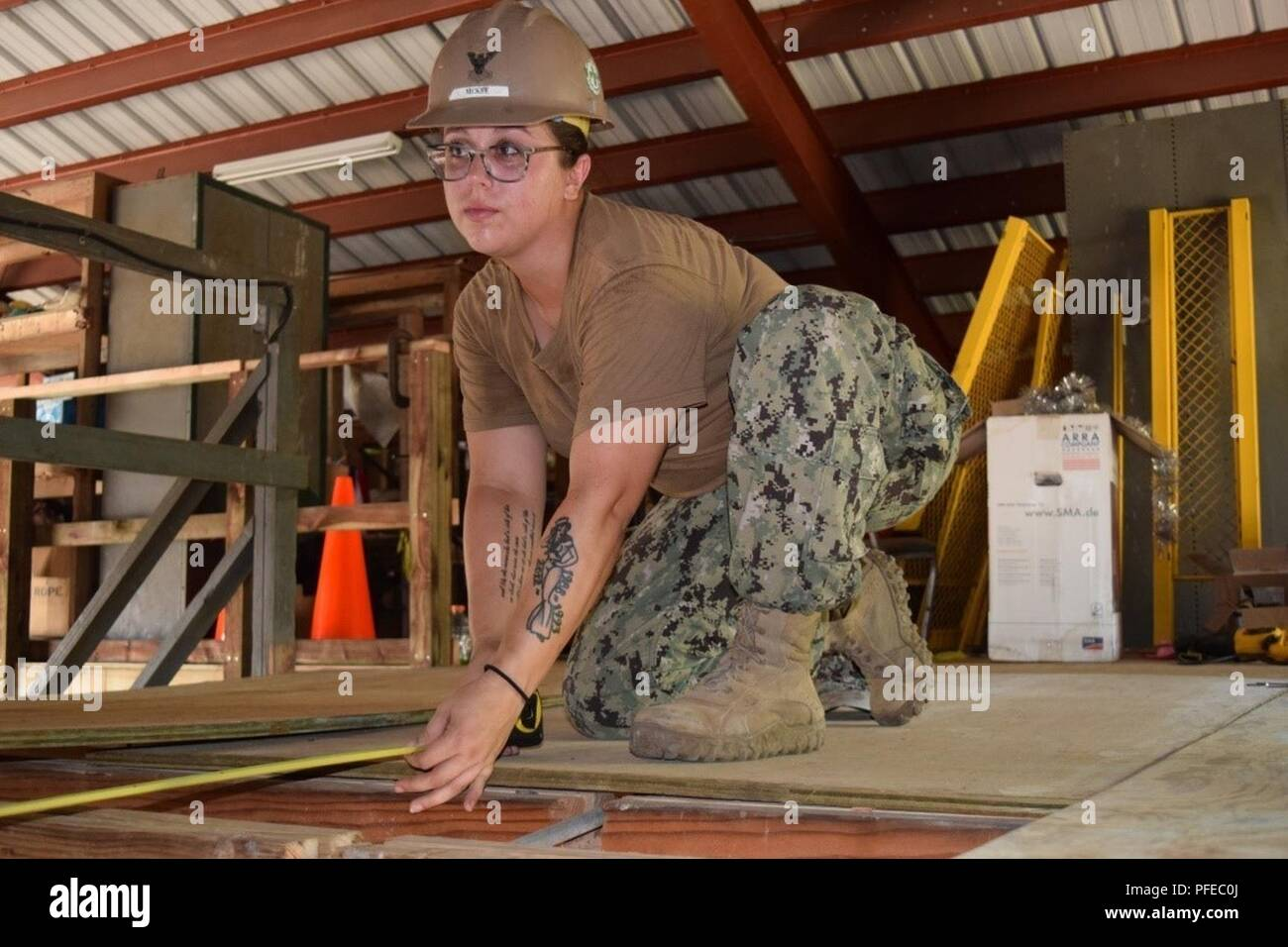 KOROR, Palau (June 5, 2018) Steelworker 2nd Class Petty Officer Shanna McKee, assigned to Naval Mobile Construction Battalion (NMCB) 5, measures the joists in preparation for laying plywood. NMCB 5 is forward deployed to execute construction, humanitarian and foreign assistance, and theater security cooperation support of United States Pacific Command. Stock Photo