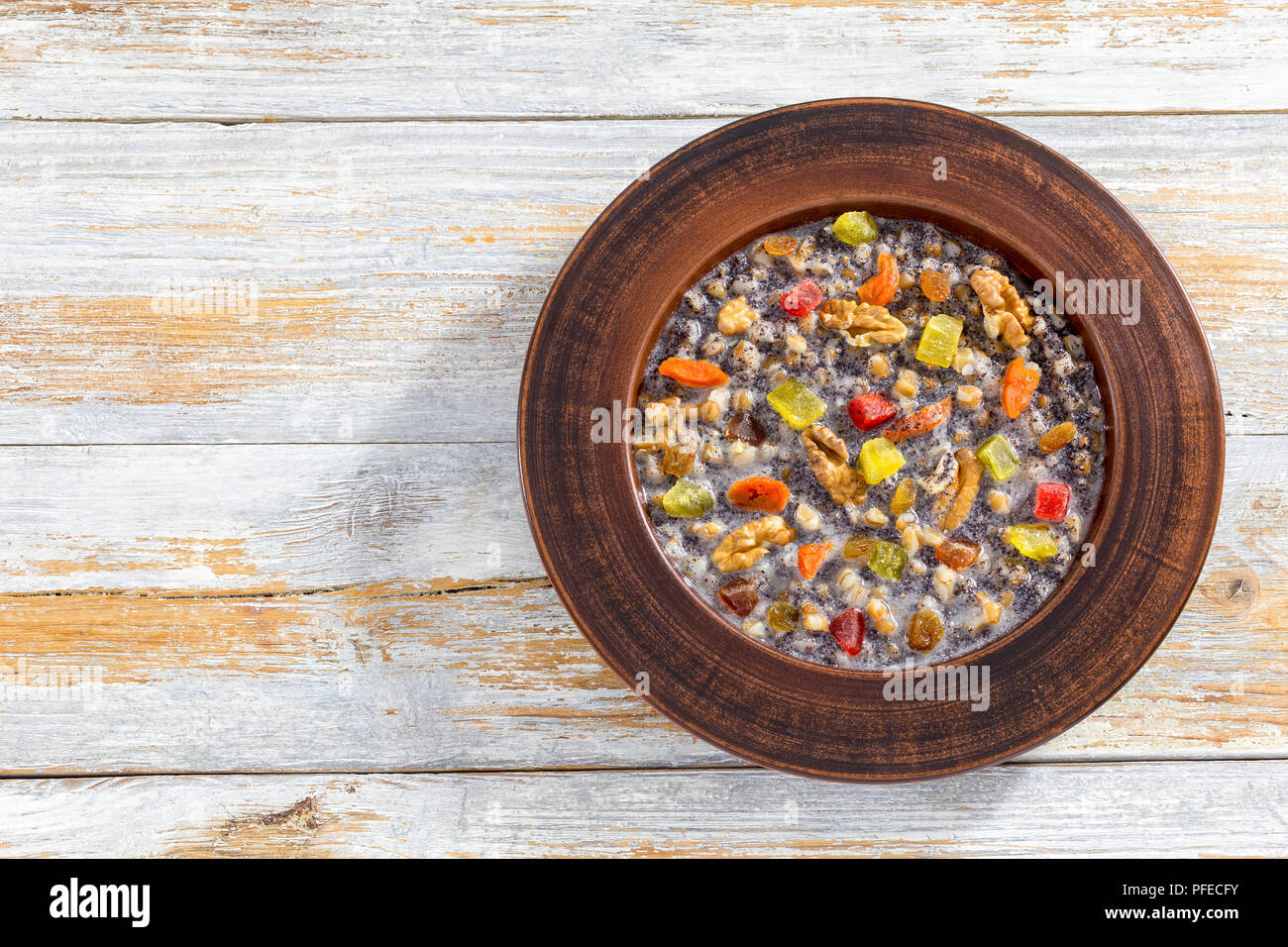 Sweet wheat kutia with nuts, poppy seeds, dried fruits. succade and honey in clay bowl on wooden planks.Traditional Christmas dish in russia and ukrai - Stock Image