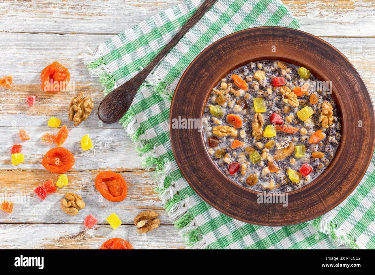 Sweet wheat kutia with nuts, poppy seeds, dried fruits. succade and honey in clay bowl with spoon on kitchen cloth on wooden planks. with ingredients  - Stock Image