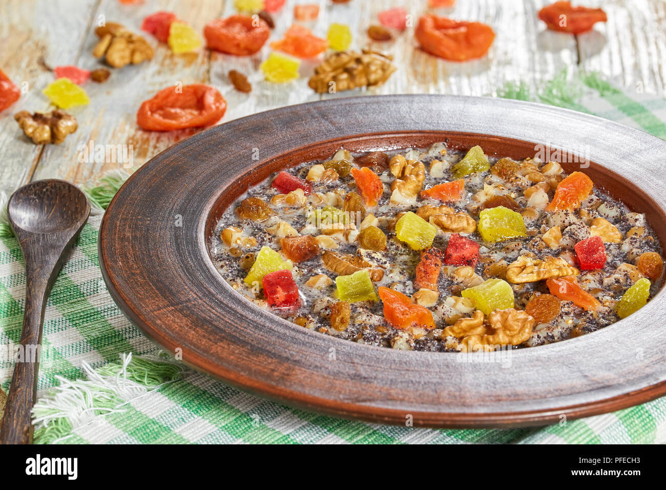 Sweet wheat dessert kutia with nuts, poppy seeds, dried fruits, succade and honey in clay bowl with spoon on table napkin on wooden planks. with ingre - Stock Image
