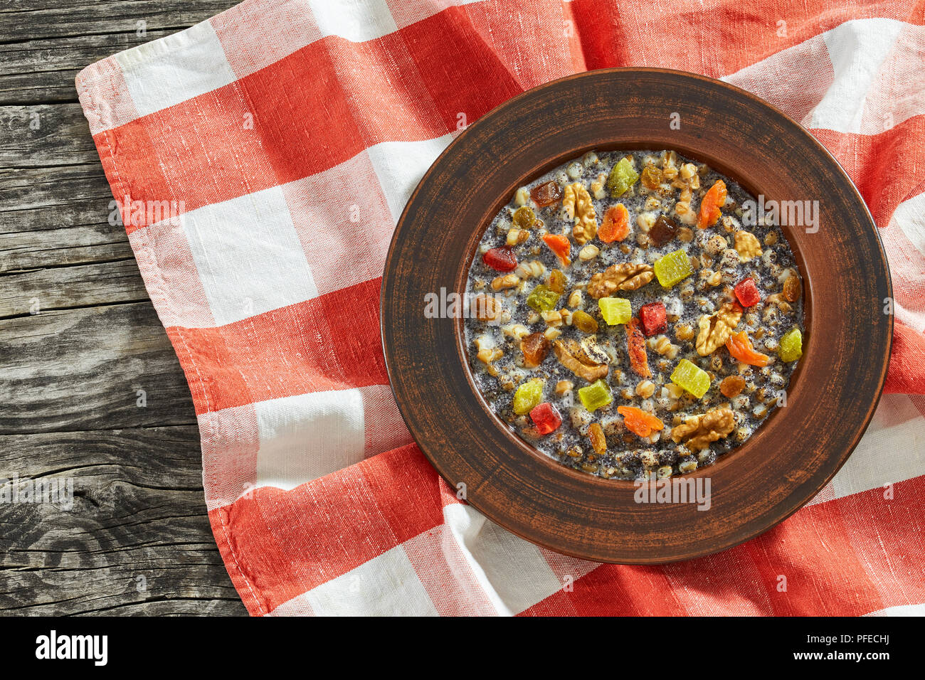 kutya or Sweet Wheat Berry Pudding, traditional Christmas dish in clay rustic bowl on table cloth on dark wooden table, view from above - Stock Image