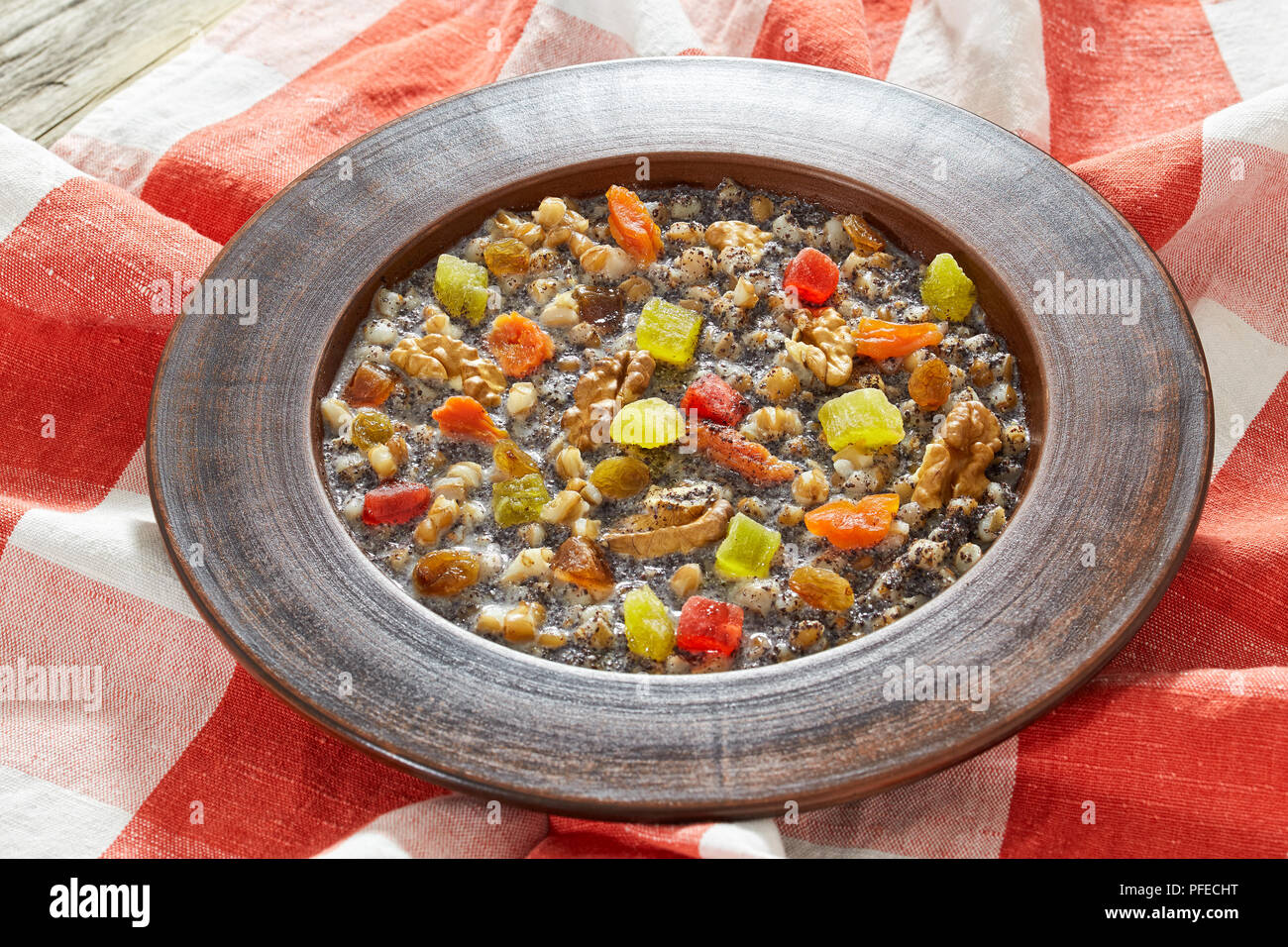 sweet winter Poppy Seed and wheat soup Kutya, traditional Ukrainian Christmas food with walnuts, raisins, dried apricot and honey, authentic recipe, c - Stock Image