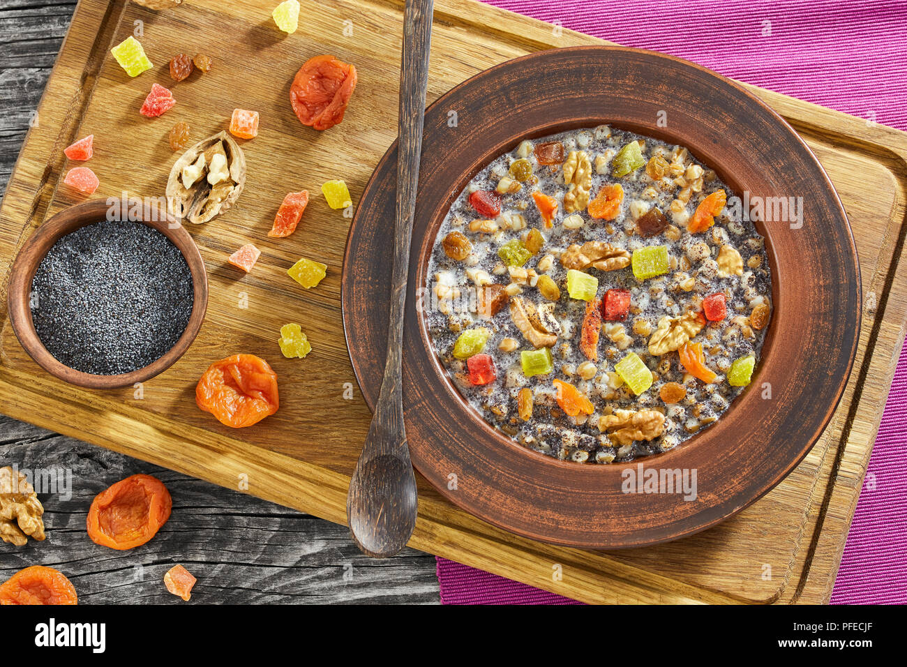 Traditional Christmas slavic dish kutia in ceramic bowl on chopping board with ingredients, view from above - Stock Image