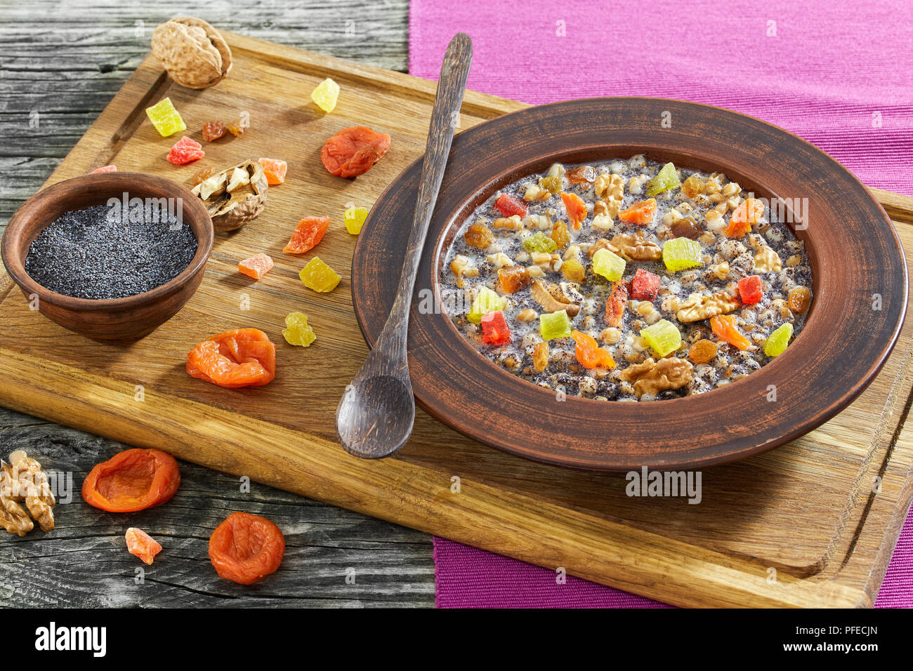 Traditional Christmas slavic dish kutia in ceramic bowl on chopping board with wooden spoon and ingredients on background, view from above, close-up - Stock Image