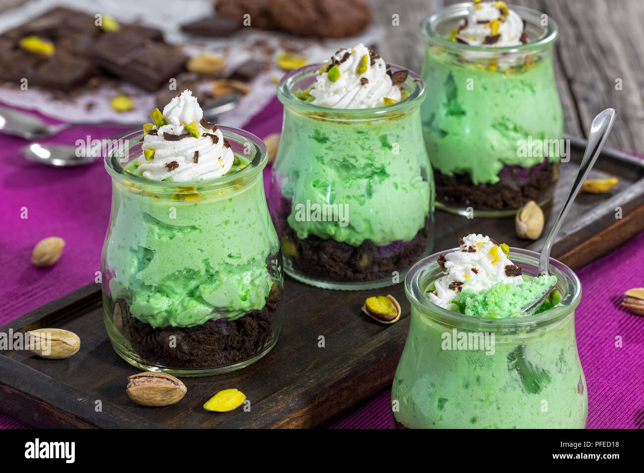 No Bake pistachio aero mousse Cheesecake Shooters with ice cream and decorated with chocolate chips - easy homemade layered delicious dessert for fest - Stock Image