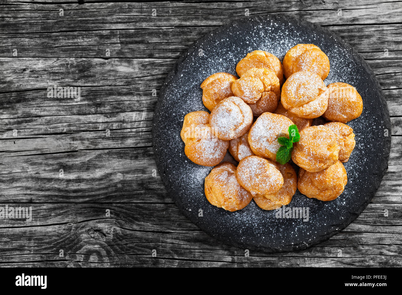 Delicious profiteroles filled with cream on slate plate,  dusting of powdered sugar, on old dark wooden table, view from above - Stock Image