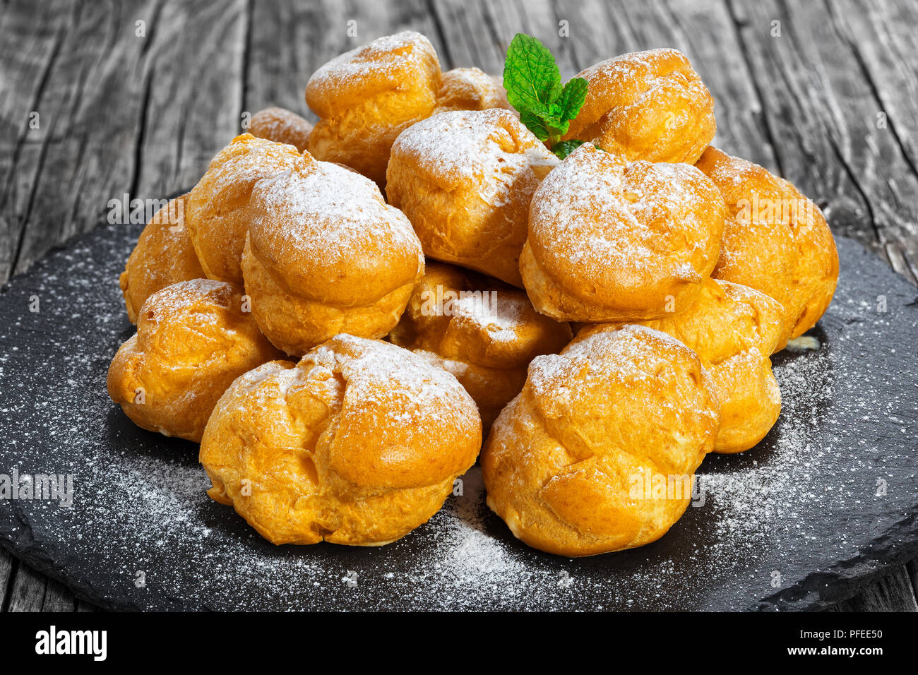 Delicious profiteroles filled with cream on slate plate,  dusting of powdered sugar and decorated with mint, on old dark wooden table, close-up - Stock Image
