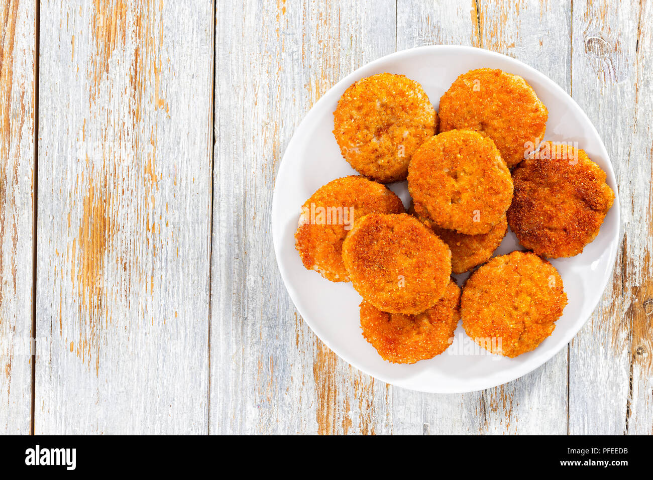 juicy delicious corn breaded meat cutlets on white plate on old wooden peeling paint planks, view from above - Stock Image