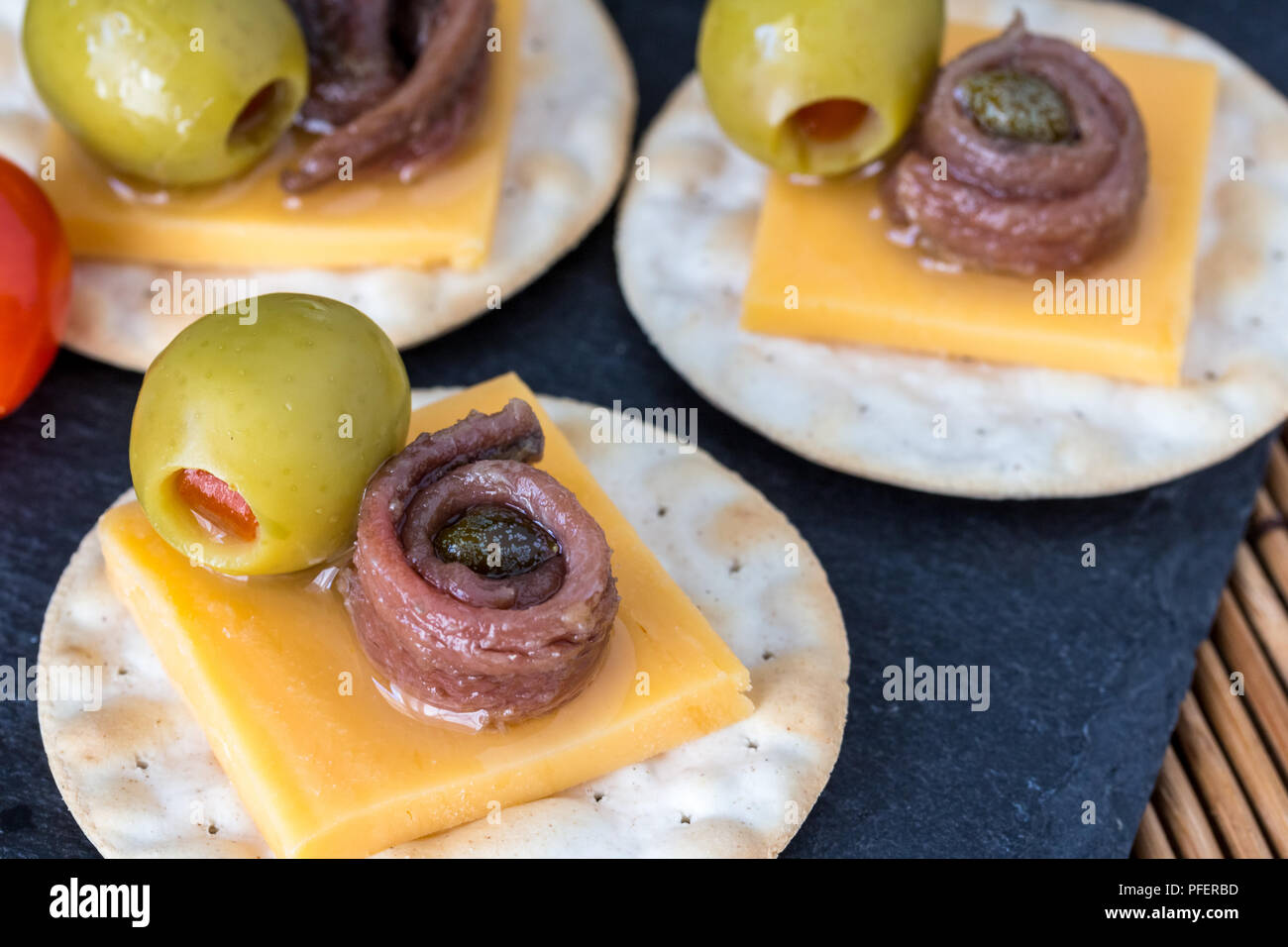 Anchovy on crackers with stuffed olives - Appetizer background with selective focus - Stock Image