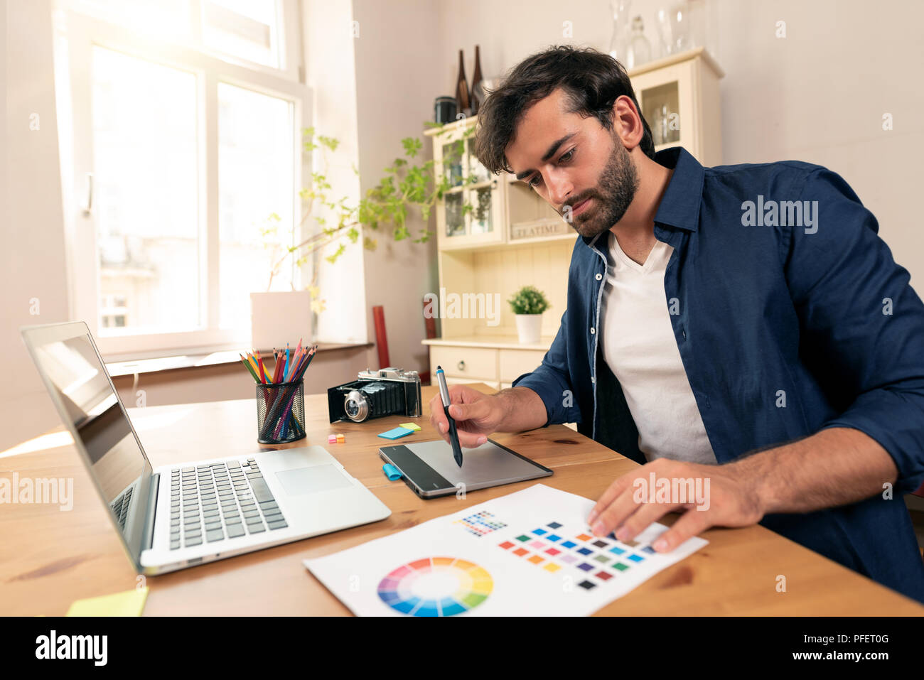 Graphic designer working on digital tablet. Freelancer working at home. - Stock Image