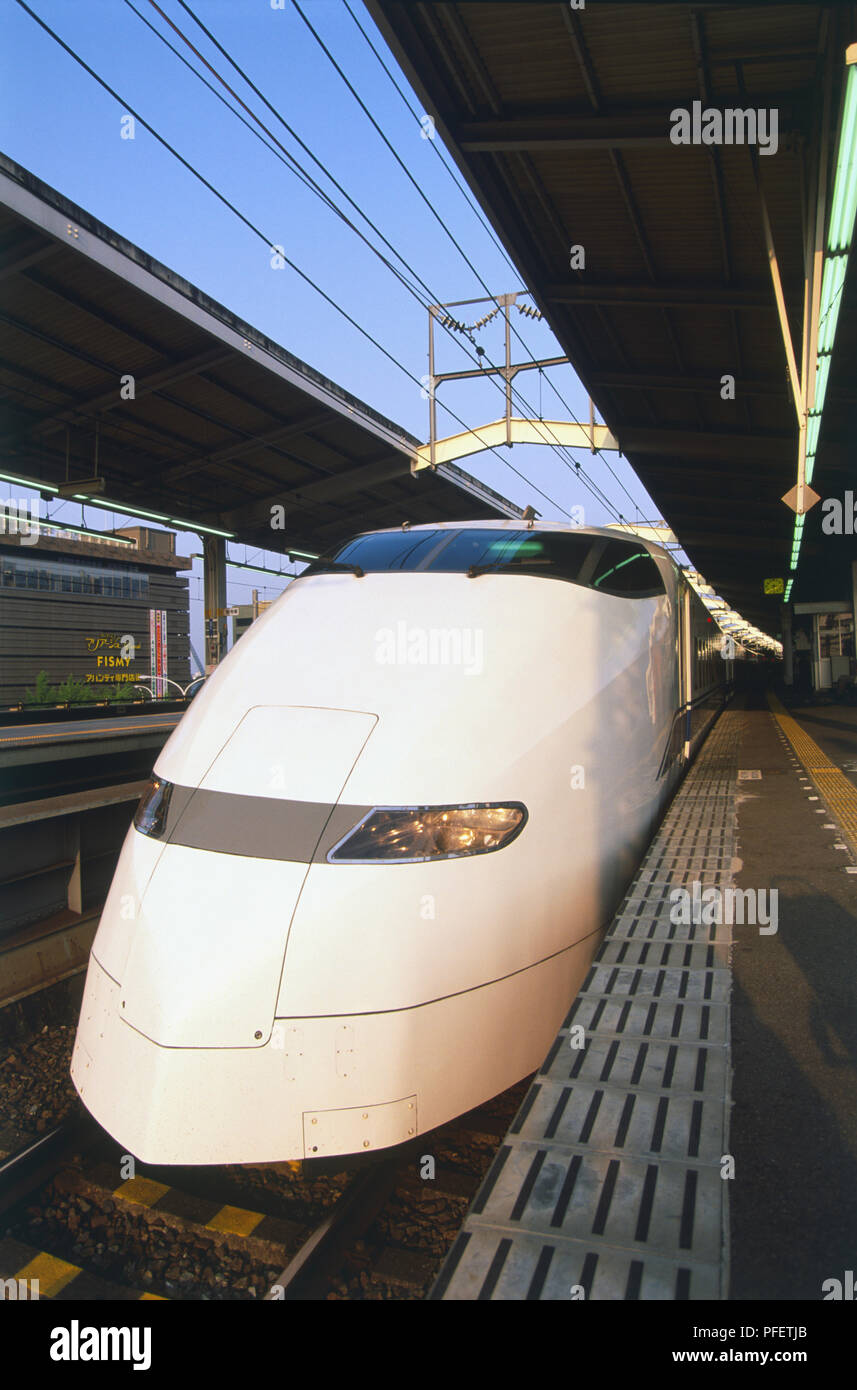 Japan, areodynamically shaped nose of Shinkansen or Bullet Train standing at empty platform, front view. - Stock Image