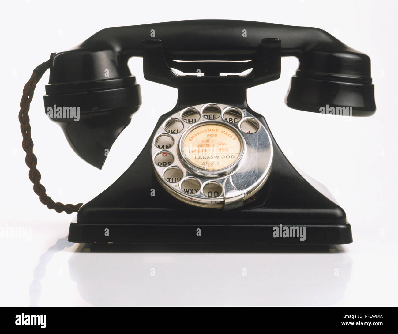 Black telephone with rotary dial, close up. - Stock Image