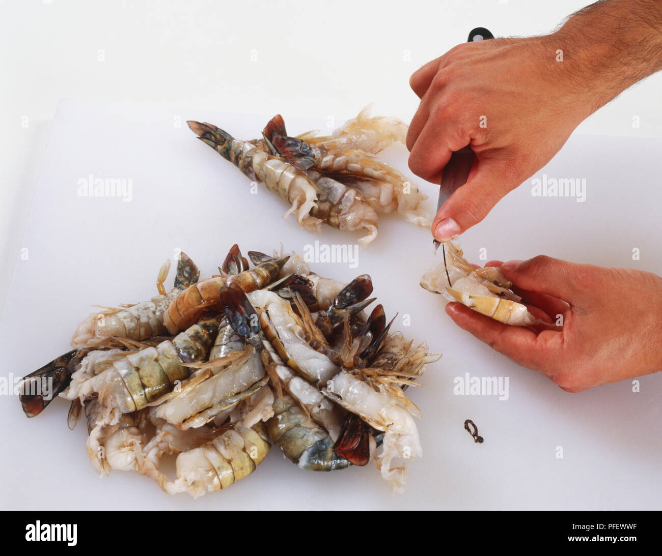 Pile of prawns, one being peeled using a knife - Stock Image
