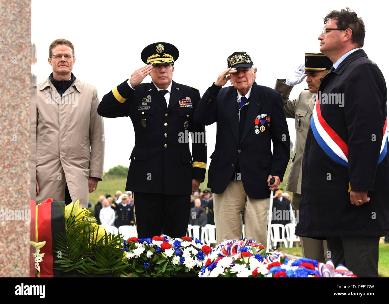 SAINTE-MARIE-DU-MONT, France (June 6, 2018) D-Day veteran John Roman (center) and Maj. Gen. Mark W. Palzer, commander of the 79th Theater Sustainment Command (center left), salute for the playing of French and U.S. taps during the Utah Beach Federal Monument Ceremony. This year marks the 74th anniversary of Operation Overlord, the Allied invasion of Normandy on June 6, 1944 -- most commonly known as D-Day. An epic multinational amphibious and airborne operation, D-Day forged partnerships and reinforced transatlantic bonds that remain strong today. Overall, U.S. service members from 20 units in Stock Photo