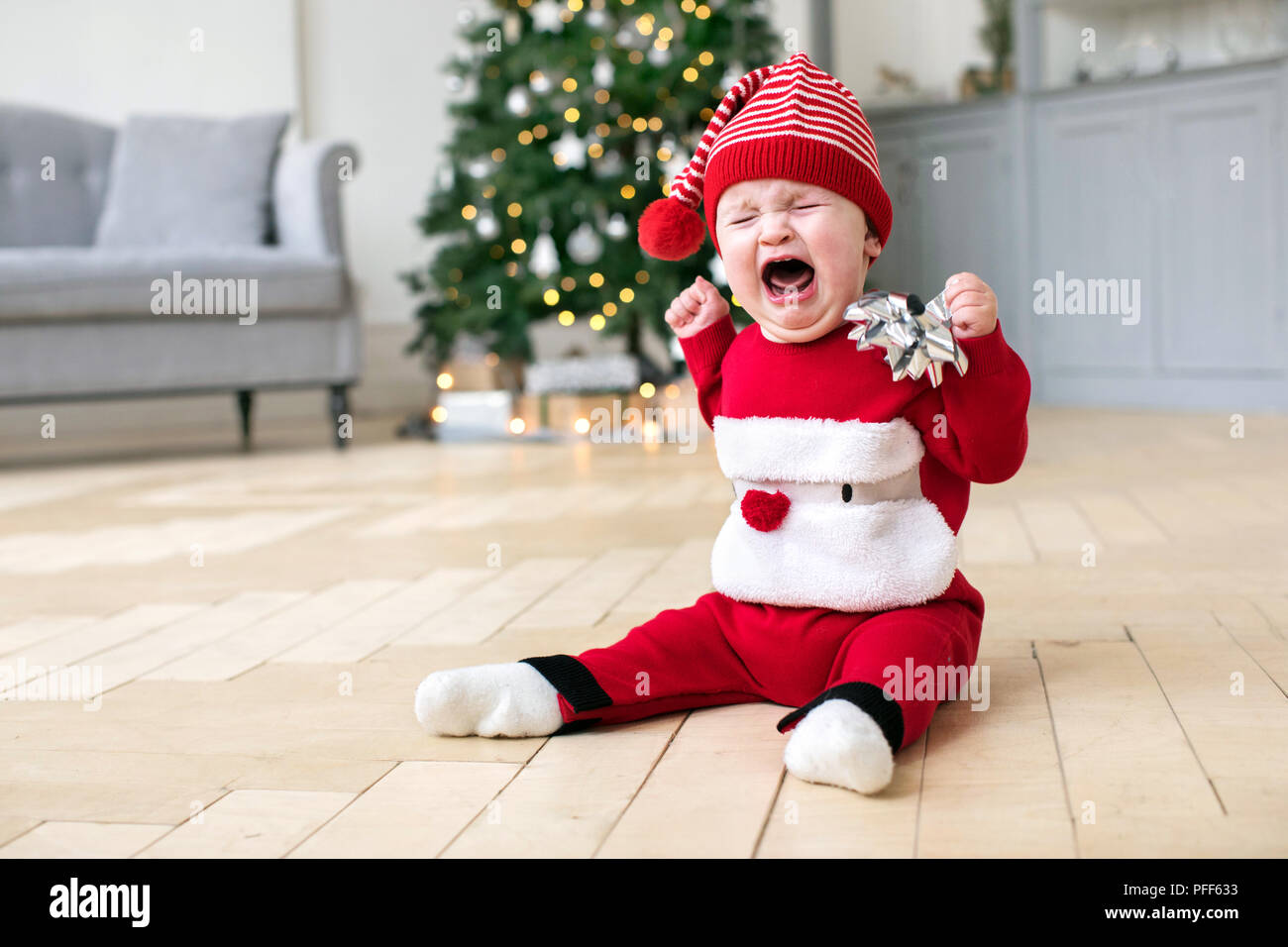 Baby in Cristmas costume crying on floor Stock Photo