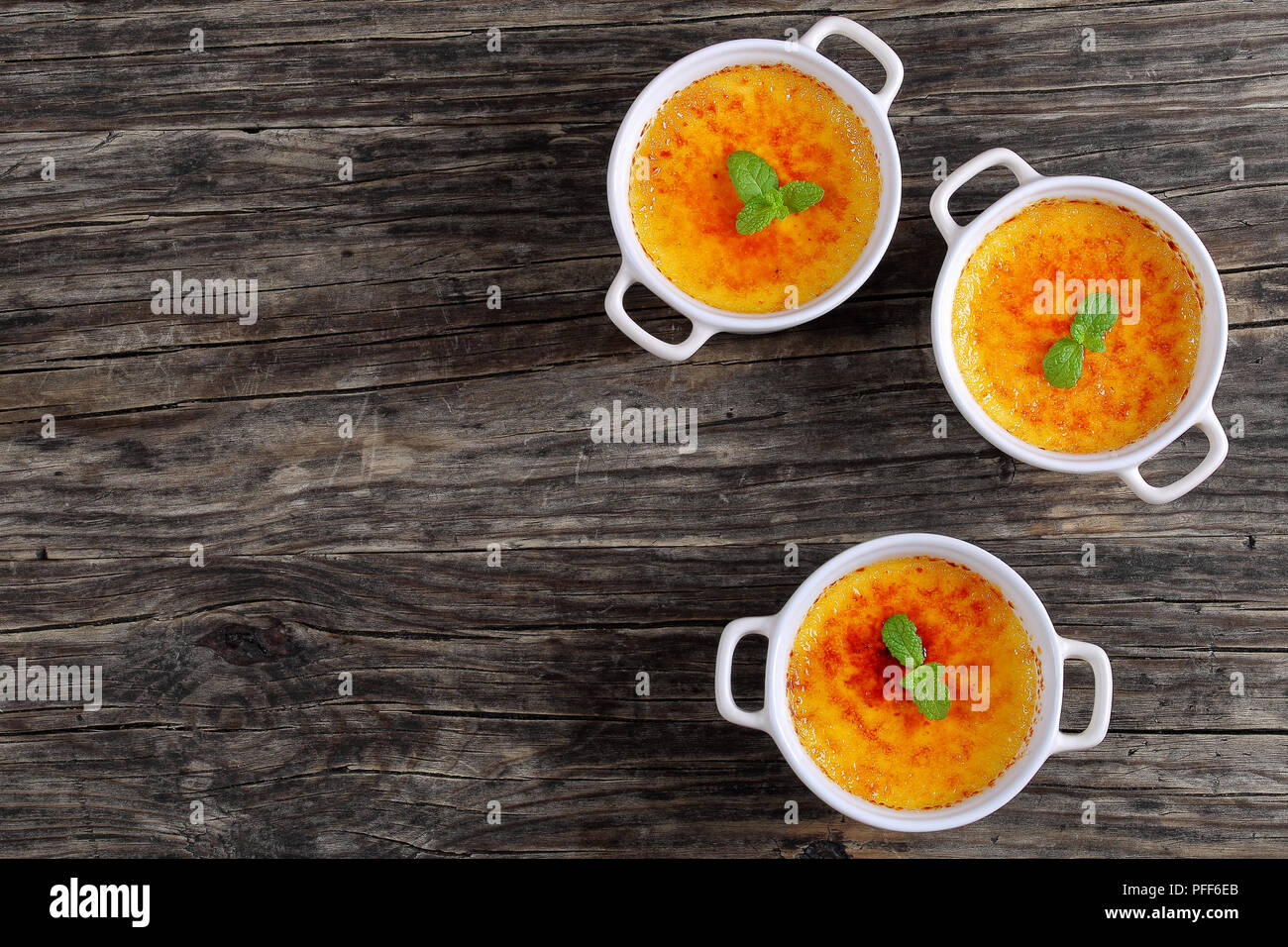 Creme brulee - french dessert of custard topped with caramelized sugar and decorated with mint leaves in white ceramic souffle dishes on old rustic ta Stock Photo