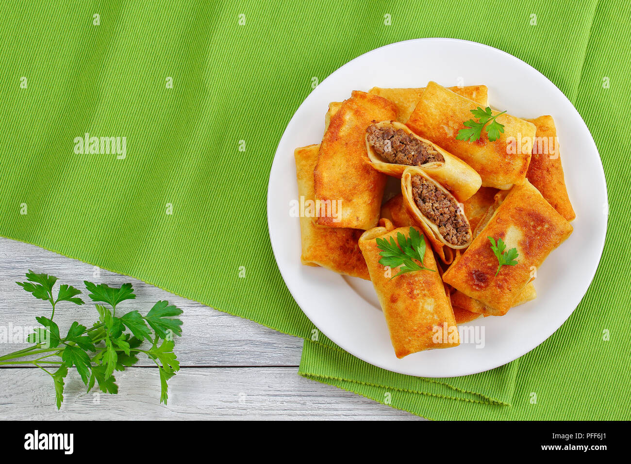 fried in olive oil delicious Crispy and hot Crepes filled with minced liver and rolled up on white plate on old wooden table, view from above Stock Photo
