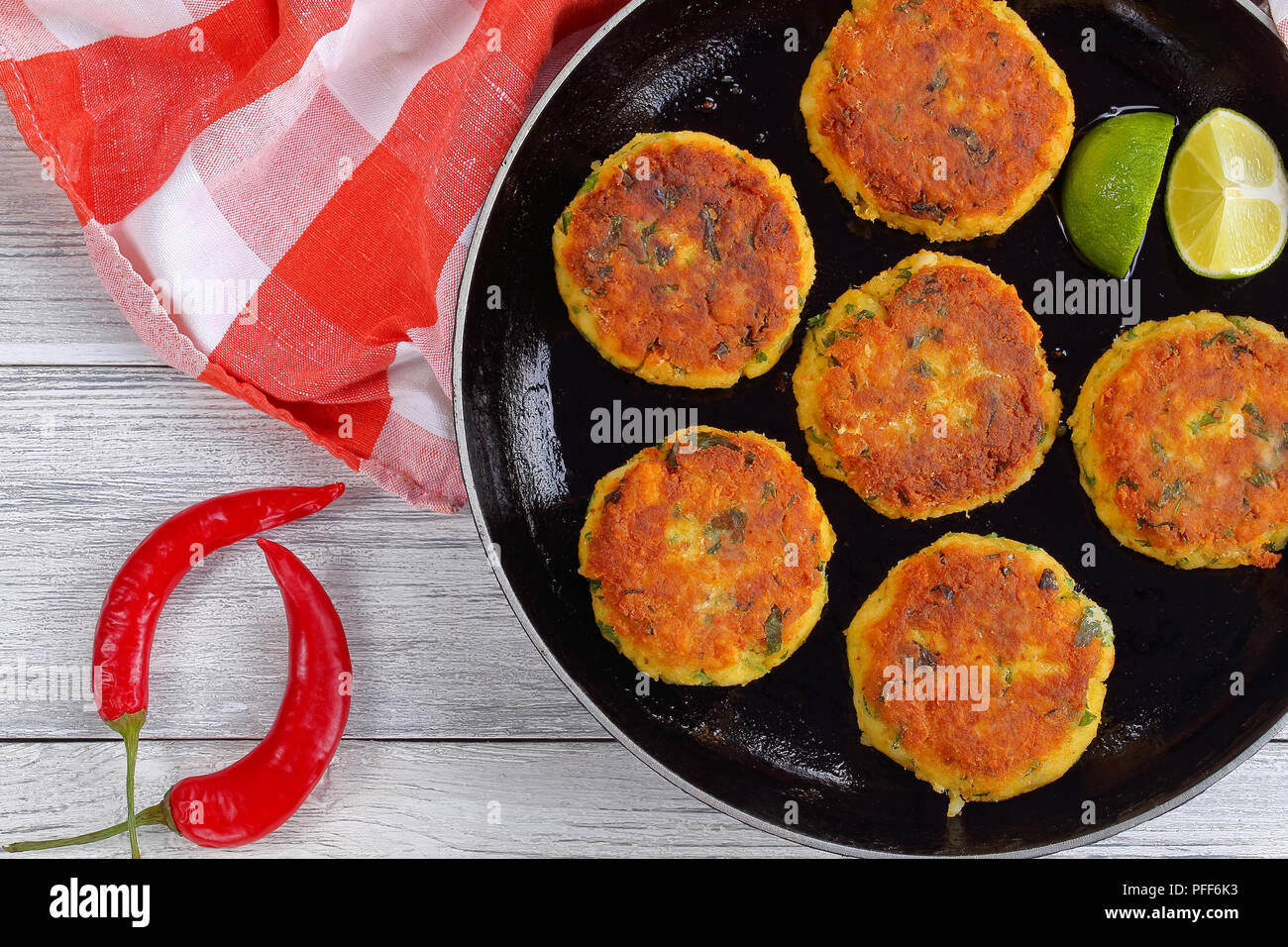 delicious fresh fried homemade fish cakes with mashed potato on skillet with lime slices, on wooden table with kitchen towel, chili peppers, authentic - Stock Image