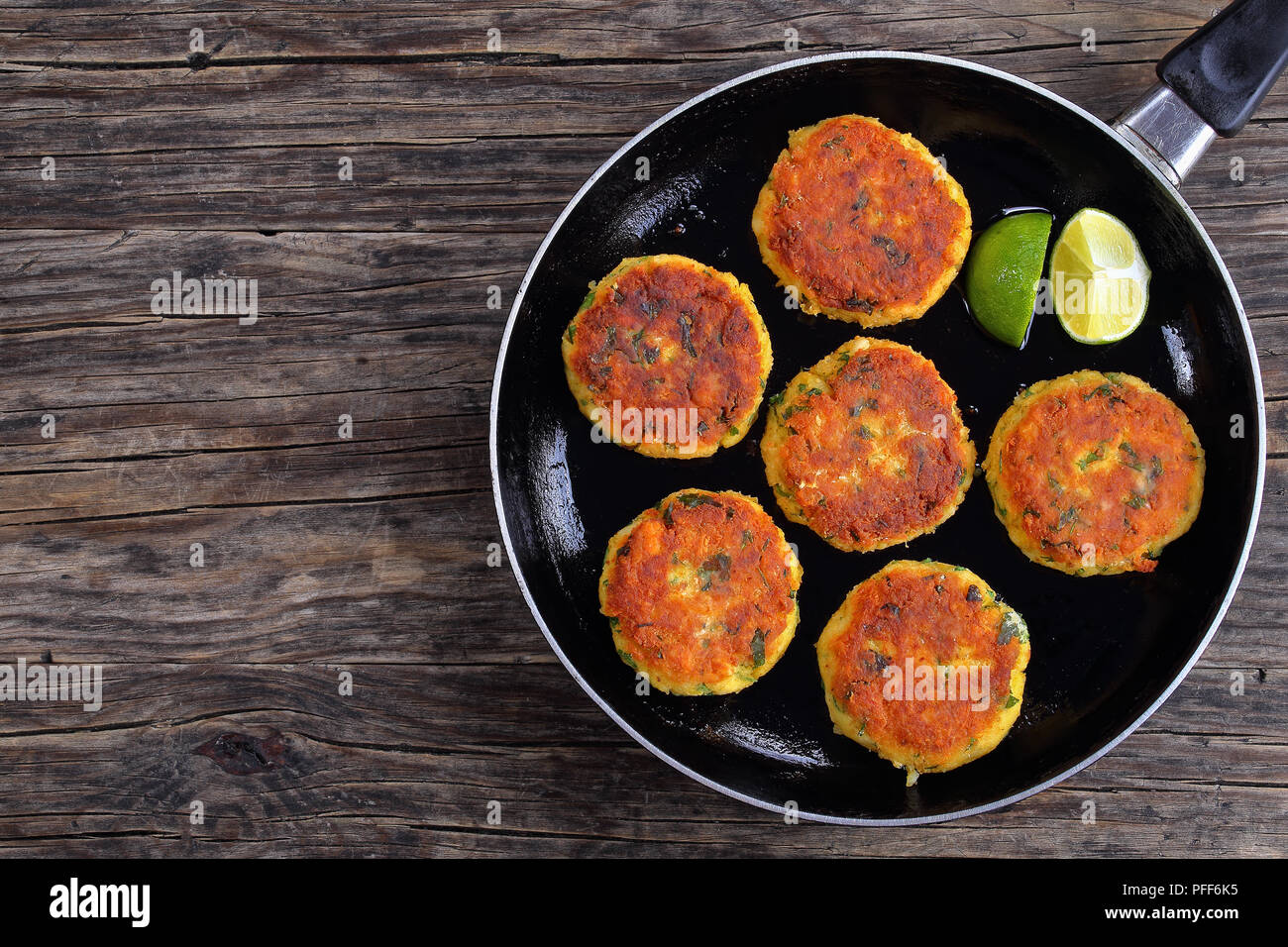 delicious fresh fried homemade fish cakes with mashed potato on skillet with lime slices, on dark wooden table, classic recipe, view from above - Stock Image