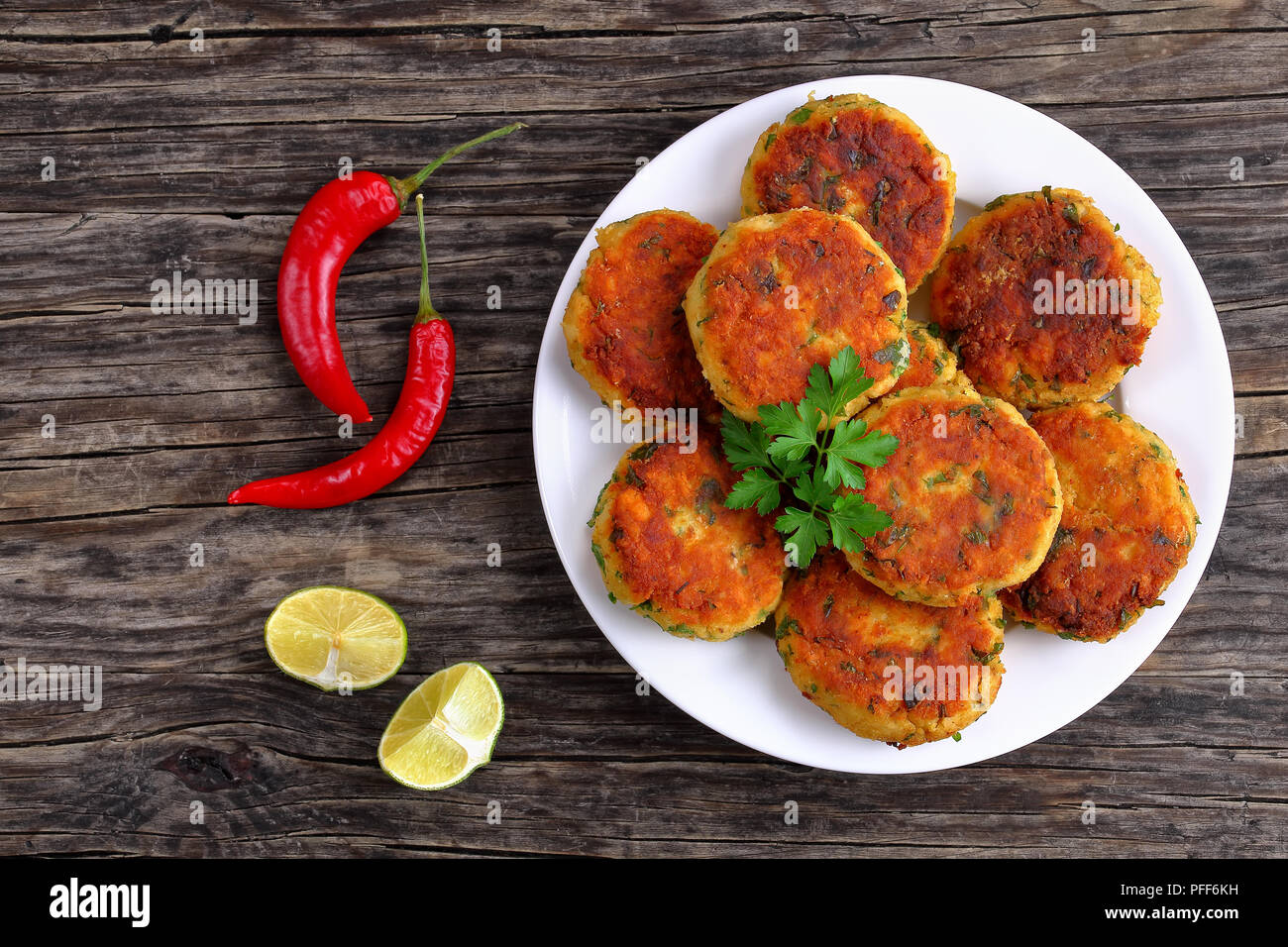 delicious fresh fried homemade fish cakes with mashed potato on plate with lime slices on dark wooden table, classic recipe, view from above - Stock Image