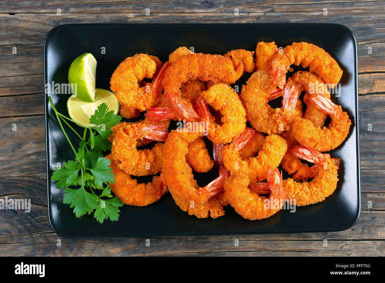 delicious deep fried breaded shrimps on black plate with lime wedges and coriander leaves, horizontal view from above, close-up - Stock Image