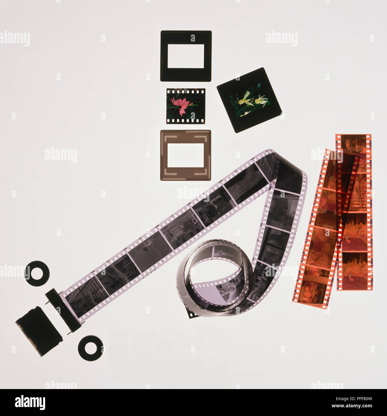 Roll of black and white negative film, strips of coloured negative film, coloured slides in and out of cases, view from above. - Stock Image