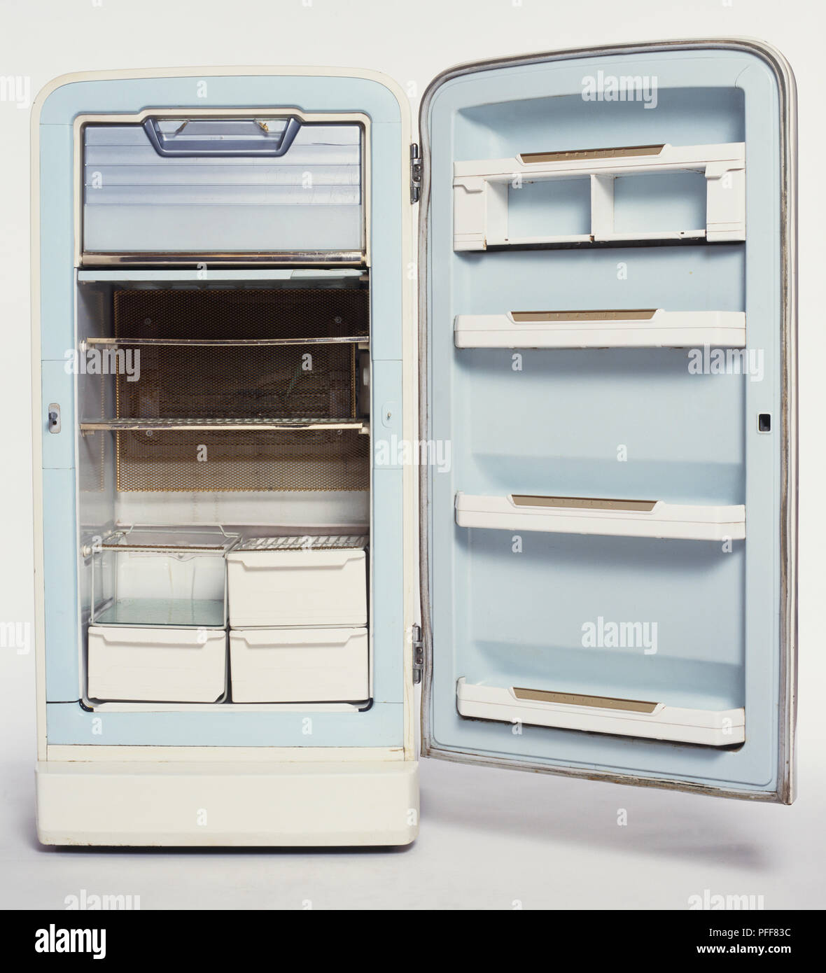 Empty 1950s fridge with its door wide open, front view. - Stock Image