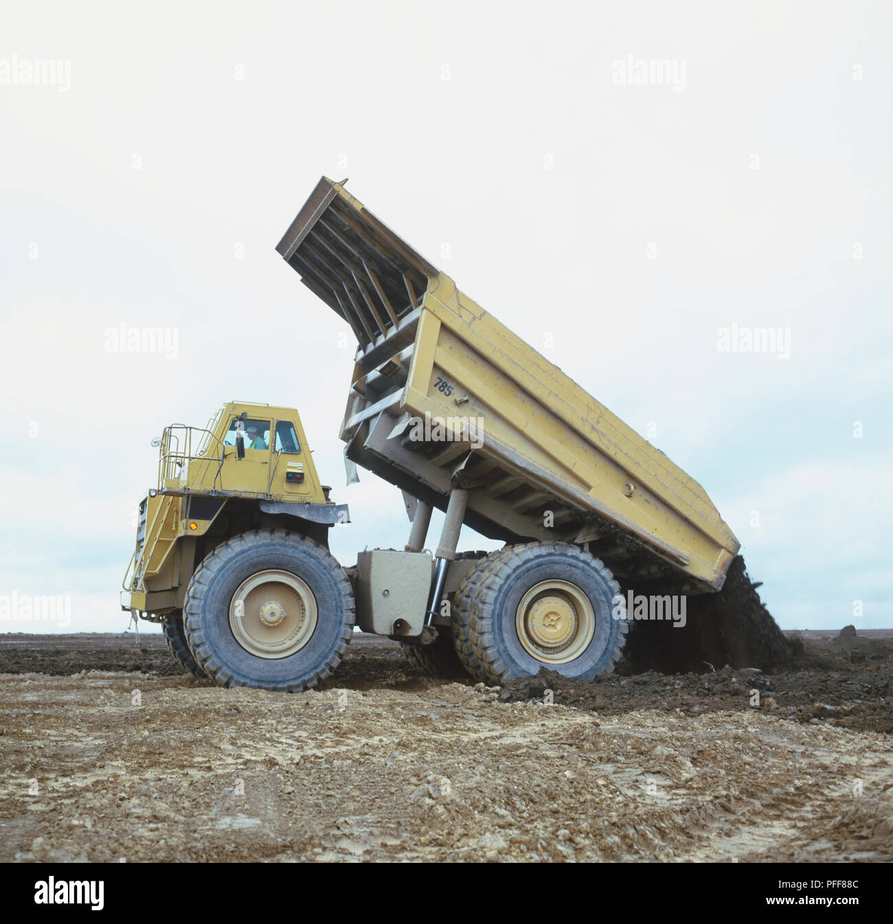 Yellow truck with tilted rear dumping rubble, side view. - Stock Image