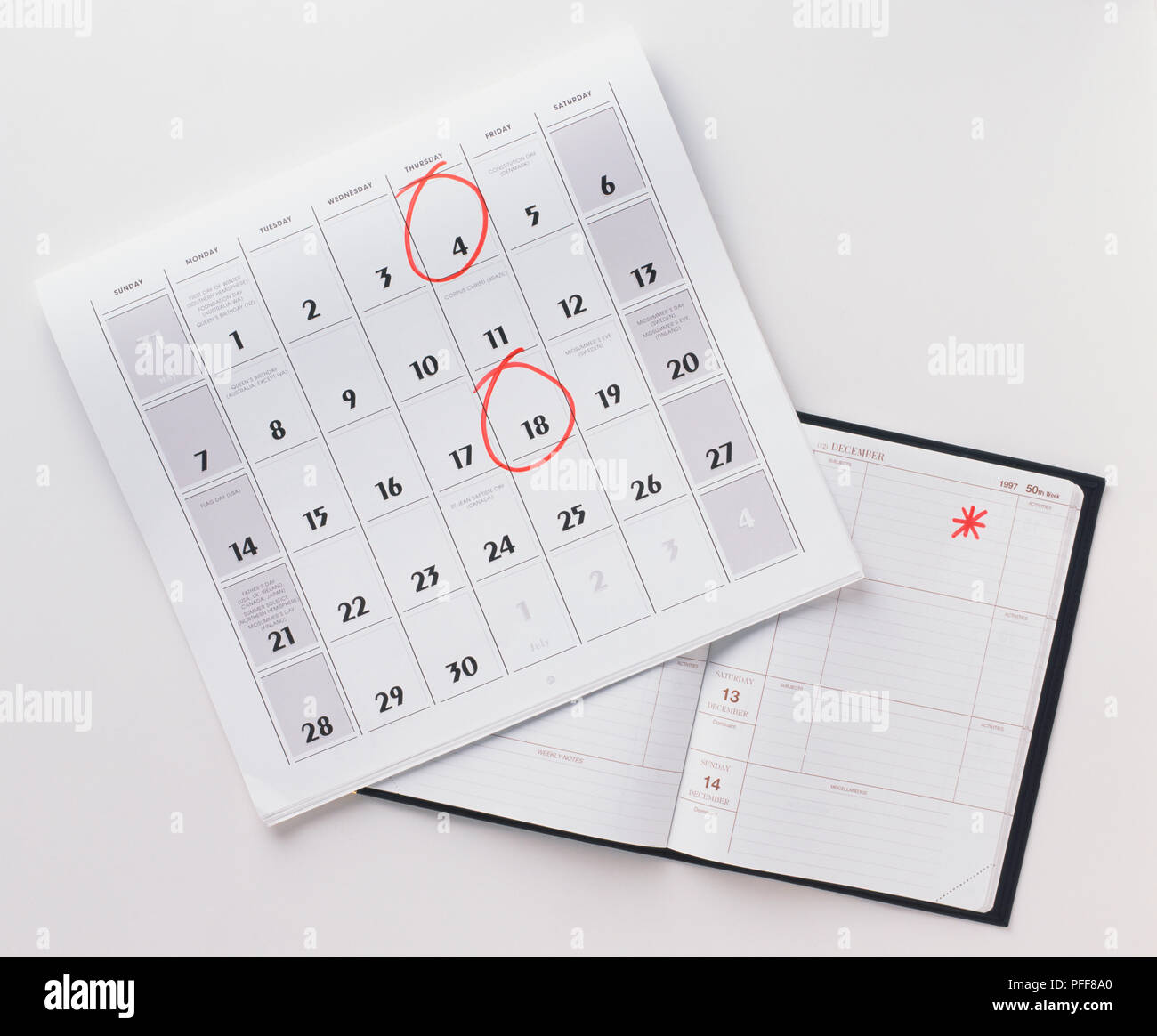 Calendar page and open diary, with specific days marked in red. - Stock Image