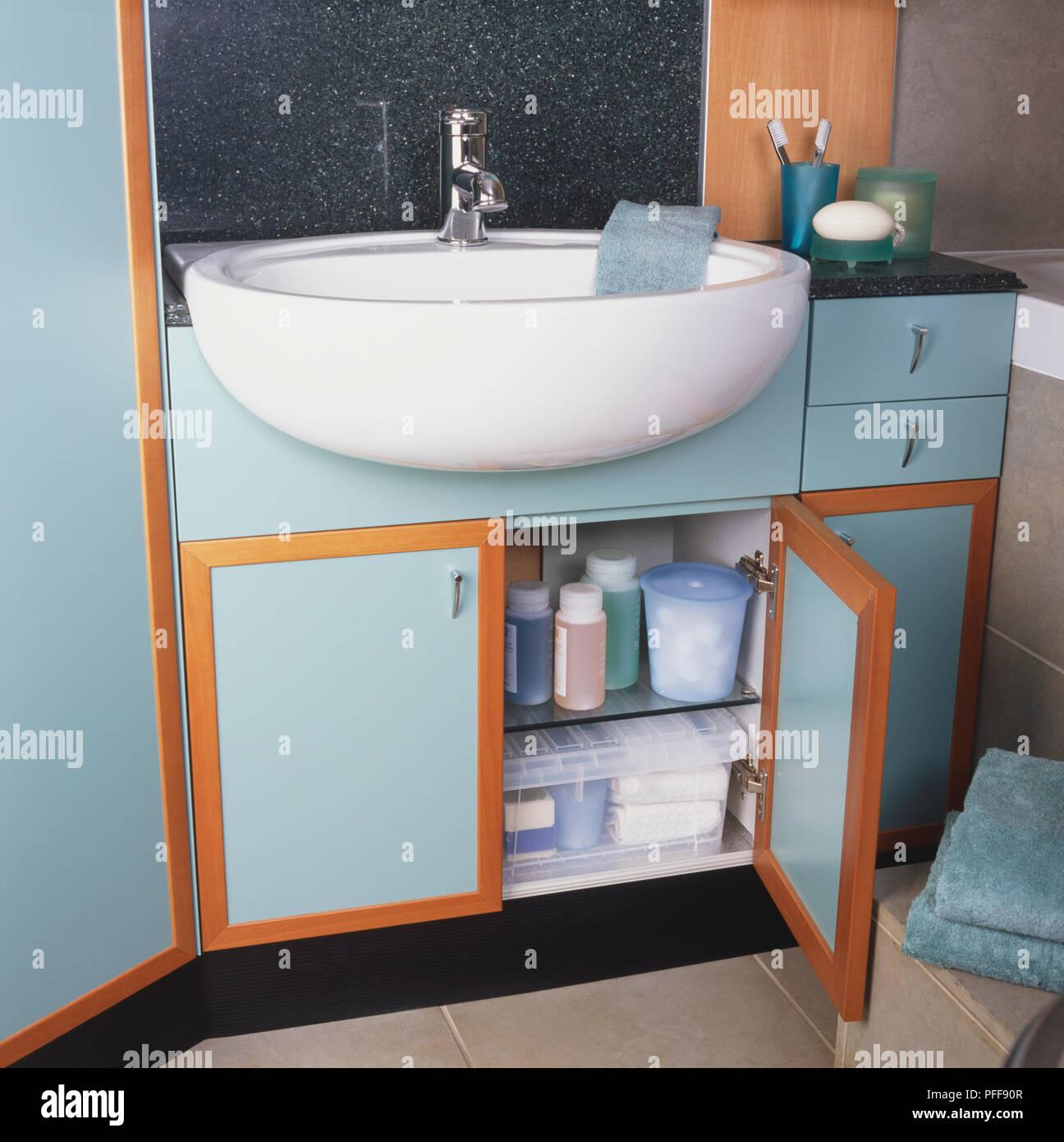 Bathroom sink built into storage unit with opnened cupboard door ...