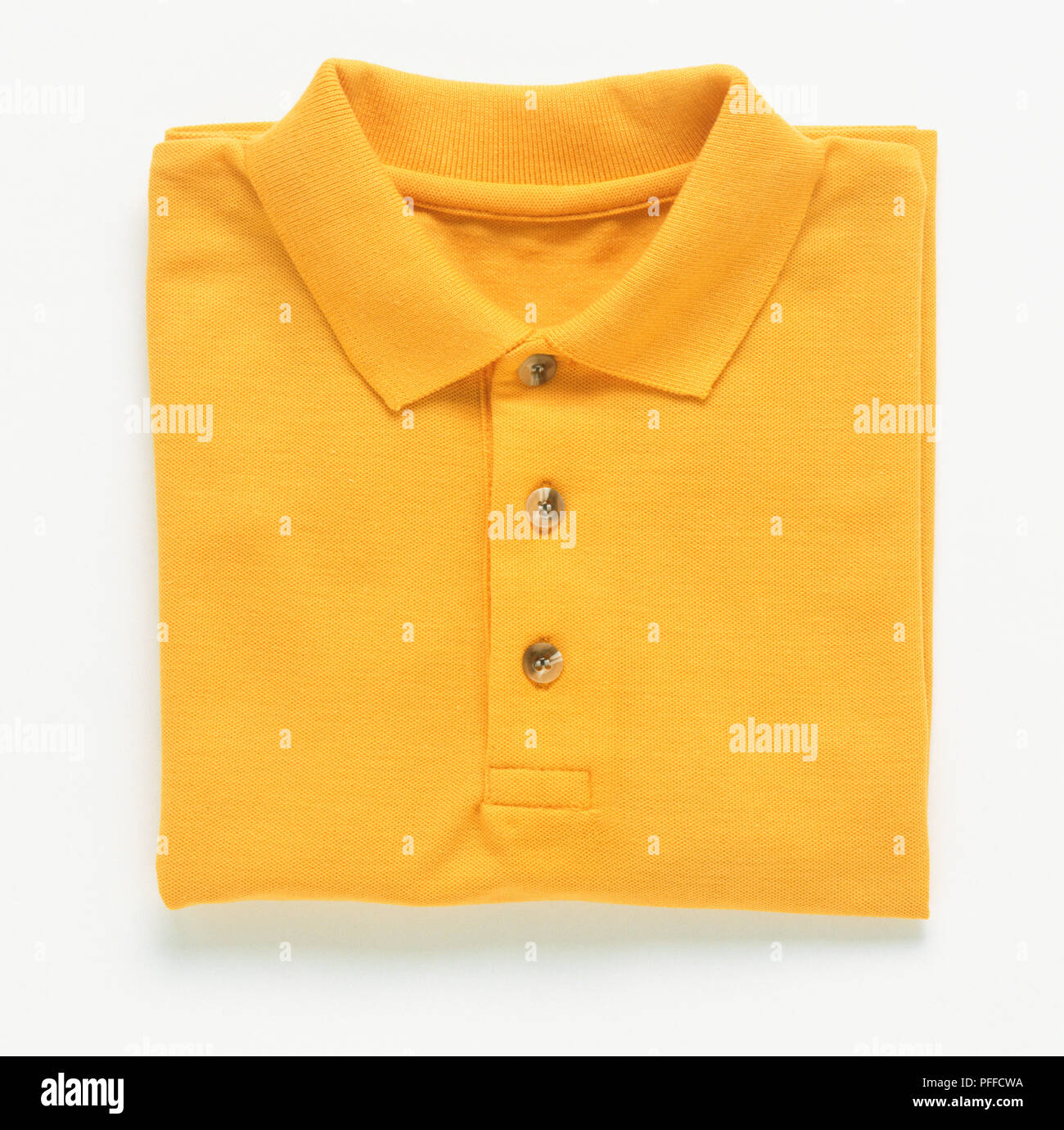 Folded yellow t-shirt. - Stock Image