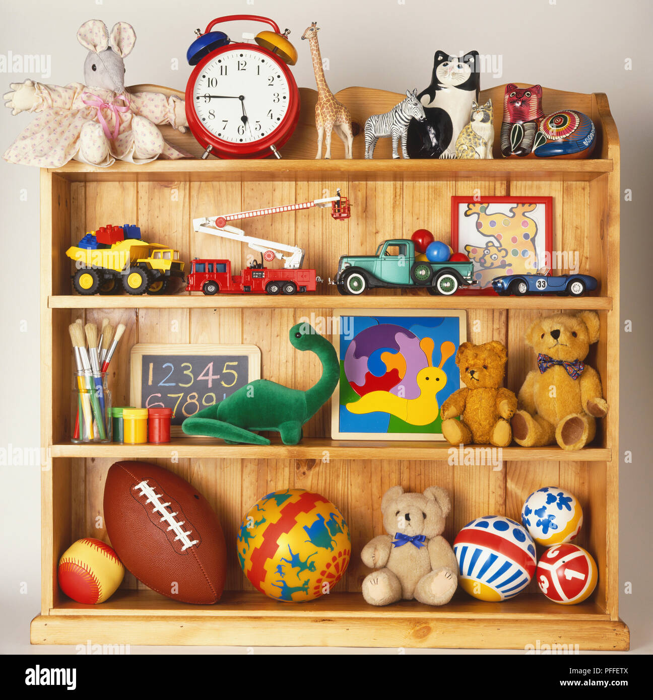 Wooden bookcase stacked with toys including rubber balls, cuddly ...