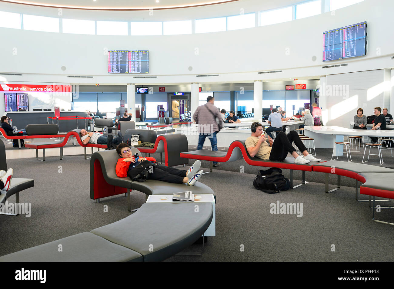 Passengers relaxing on modern seats at Brisbane Airport, Queensland, QLD, Australia - Stock Image